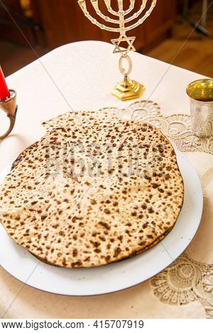 Matzah For Passover Seder On The Table Next To The Symbols Of Judaism.