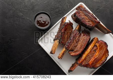 Smoked beef ribs with bone and barbecue sauce on a white square plate, top view, rustic black background. Roasted beef ribs with bone, copy space.