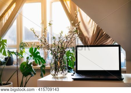 A Home Workplace With White Screen Laptop For Mockup, Blooming Branches In A Vase On The Desk With R