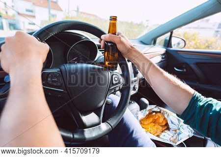 Young Drunk Man Drives A Car With A Bottle Of Beer. Driving Under Alcohol Influence. Drunk Driving
