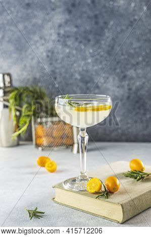 Gin And Tonic Cocktail With Kumquat Fortunella In Glass Of Champagne On Light Gray Table Surface. Cl