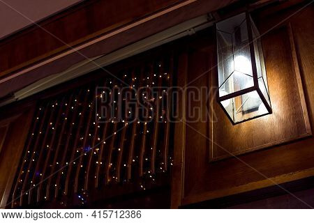 Square Glass Lantern With Electric Light Bulb On Wooden Wall Near Window With Planks Of Retro Archit