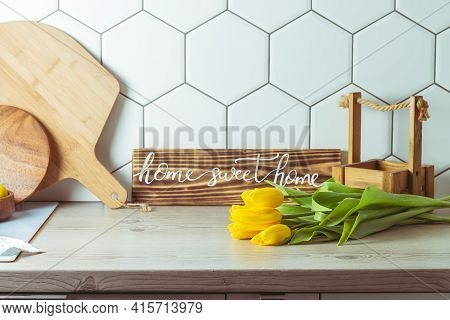 Interior Shot. Home Sweet Home Handwritten Sign On Kitchen Countertop Next To Yellow Tulip Bouquet A