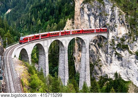 Passenger Train Crossing The Landwasser Viaduct In Switzerland