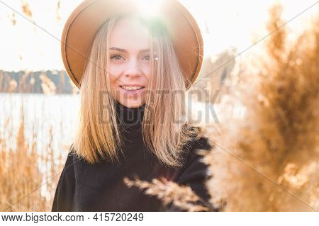 European Blonde Woman With Beige Hat In Black Sweater In The Countryside. Golden Hour, Cottagecore.