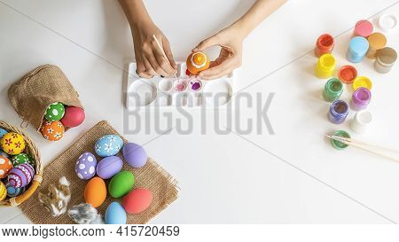 Top View Of Asian Woman Hand Painting Eggs For Eastertime At Home. Family Preparing For Easter.