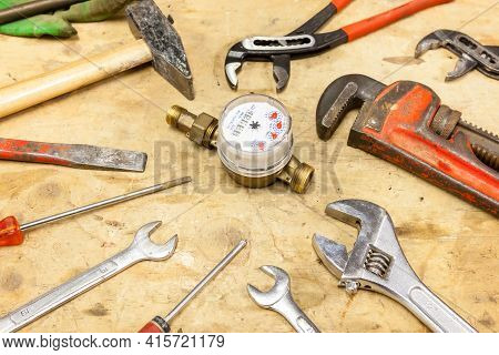 On A Work Table In The Workshop There Are Tools And A Water Meter For A Plumber