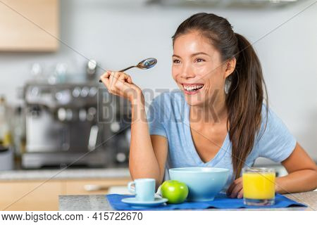 Breakfast eating young Asian woman happy at home kitchen morning meal for healthy start of day. Ethnic model portrait.