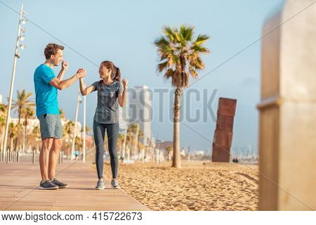 Friends teamwork interracial athletes couple happy of strong success in reaching goal training together. Runners working out outside on beach outdoor gym.