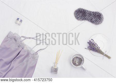 Sleep Mask, Silk Pajamas, Aroma Balsam, Dry Lavender Flowers On White Bedclothes. Aromatic Herbal Te