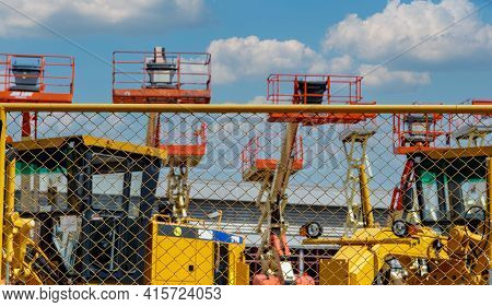 Mesh Fence Of Outdoor Warehouse Parking Lot Of Articulated Boom Lift And Motor Grader. Machine For R