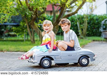 Two Happy Children Playing With Big Old Toy Car In Summer Garden, Outdoors. Kid Boy Pushing And Driv
