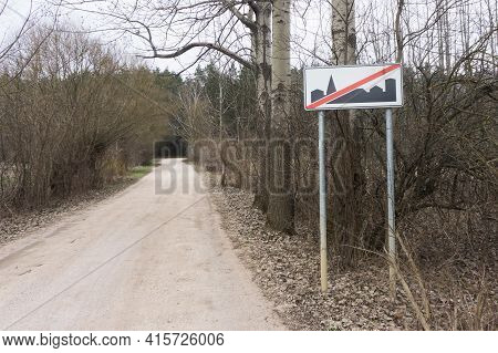 End Of Built-up Area Road Sign Background. Empty Sand Road And Rural Agriculture Fields. Car Travel