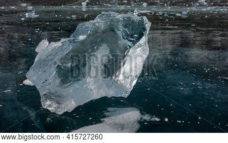 Shiny Transparent Shard Of Ice Close-up. Sharp Edges, Bizarre Shape. Reflection On The Smooth Frozen