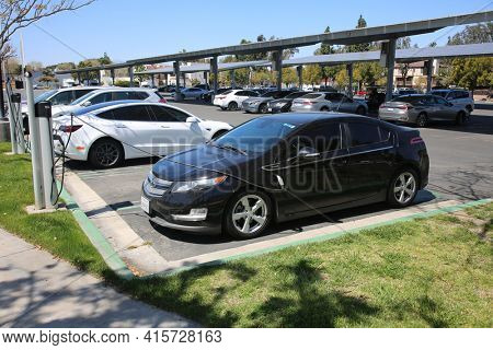 March 31, 2021 Fullerton California - USA: An Electric Car parked and having the battery recharged in a Parking Lot. Electric Cars are becoming more common than before. Editorial Use Only