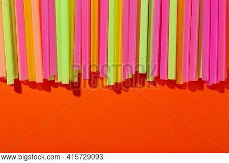 Drinking Straws On An Orange Background. Cocktail Straw. Space For Text. Top View.