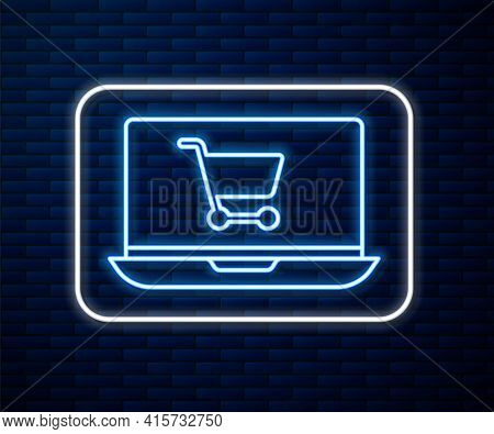 Glowing Neon Line Shopping Cart On Screen Laptop Icon Isolated On Brick Wall Background. Concept E-c