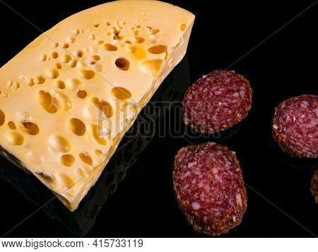 A Piece Of Hard Cheese And A Sliced Sausage On A Black Background. Hard Cheeses. Meat Sausage. Milk