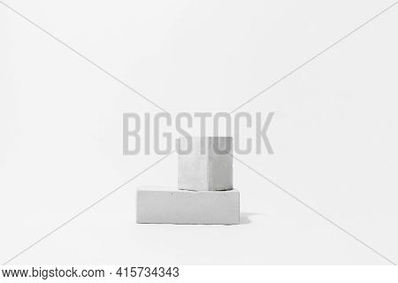 Gray Cocncrete Cube And Parallelepiped Shaped Pedestals On White Background With Copy Space, Side Vi