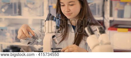 Female Teenage Student In Science Class With Experiment, Young Woman Student In Science Class With Microscope end Microscope slide