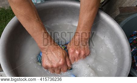 Elder Arms And Fists Of 80s Woman Washing Clothes In Old Aluminium Basin With Soap Water. Obsolete W
