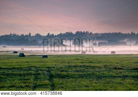 Sunrise Over A Field With Trees And Fog Floating Above The Ground