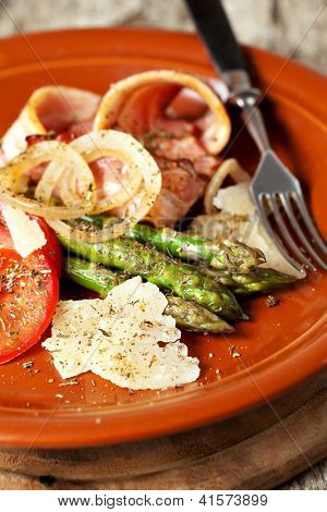 Closeup of  Grilled asparagus with ham and parmesan cheese