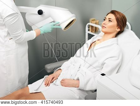 Adult Woman During Light Therapy Procedure In A Beauty Salon With Beautician To Improve Skin Appeara