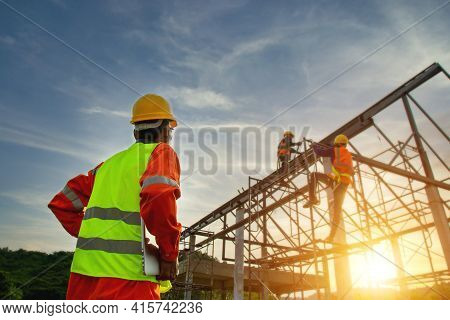 Engineer working on building site, Engineer technician watching warehouse steel roof structure , Engineer technician Looking Up and Analyzing an Unfinished Construction Project.