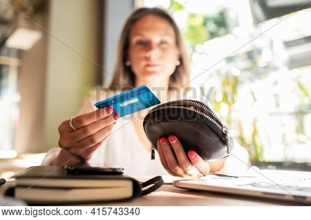 Beautiful Blonde Girl In A Coffee Shop Holds A Blue Plastic Card In Her Hand. .focus On Foreground