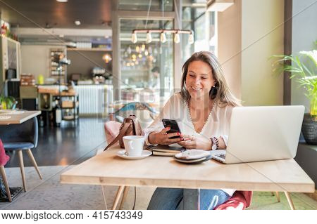 Happy Girl Typing In Her Smart Phone In A Coffee Shop.in The Table A Coffee Cup And A Laptop