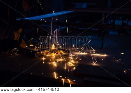A Man Welder With Construction Gloves And A Welding Mask Is Enthusiastically Working And Is Welded W