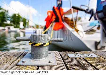 Yacht Moored With A Line Tied Around A Fixing On The Quayside, Mooring At A Pier Close Up View