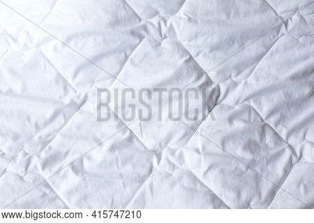 White Quilted Bedspread Background. Texture Of White Quilted Cover Design Duvet. Soft Warm Blanket.