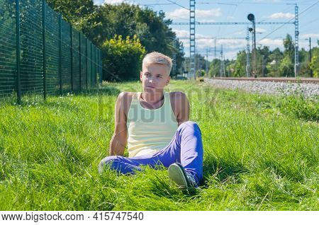Young Man In Orange Sitting On The Green Grass