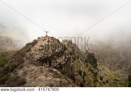 A Girl In White Clothes Stands In The Fog At The Top Of A Mountain On The Island Of Tenerife, Spain,