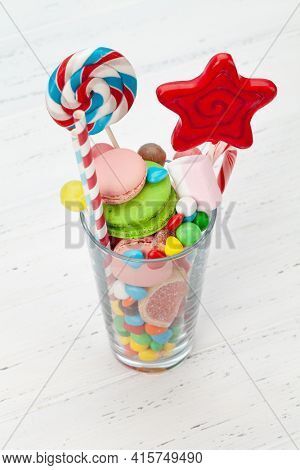 Various sweets assortment. Candy, bonbon, chocolate and macaroons in cocktail glass