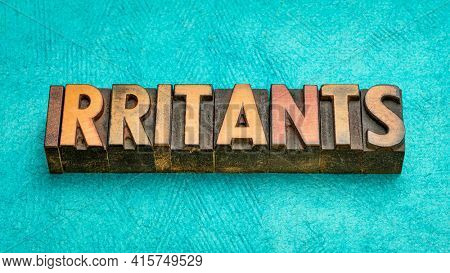 irritants word abstract in vintage letterpress wood type, a substance that causes an allergic reaction.