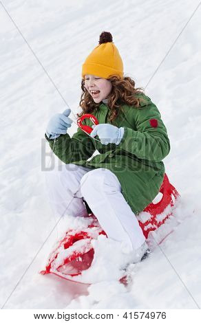 Girl Rides Sledge Down Hill