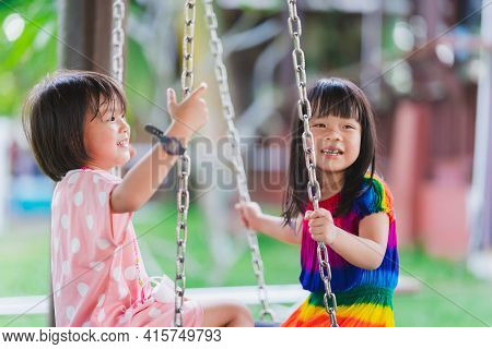 Selective Focus Of Left Girl Wear Pink Shirt. Happy Two Siblings Playing Swing. Beautiful Girls Swee