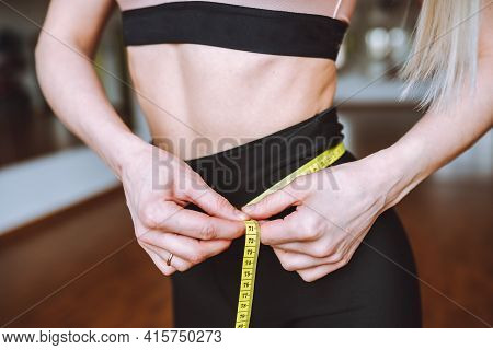 Unrecognizable Woman Measuring Her Athletic Fit Abdomenbelly With Yellow Tape. Successful Weight Los