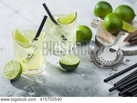Gimlet Kamikaze Cocktail In Crystal Glasses With Lime Slice And Ice On Light Background With Fresh L
