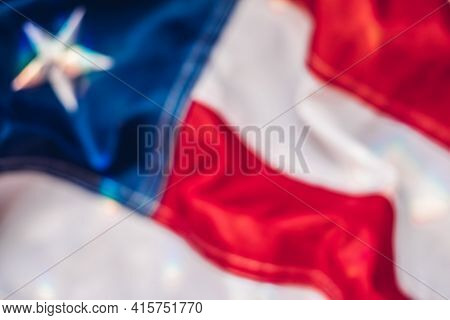 Blurred Background Image Of Fragment Of American Flag In Multicolored Sunbeams
