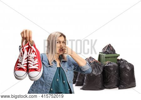 Young woman holding a pair of smelly sneakers in front of a waste bin isolated on white background