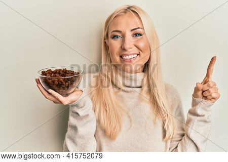 Young blonde woman holding bowl with raisins smiling with an idea or question pointing finger with happy face, number one
