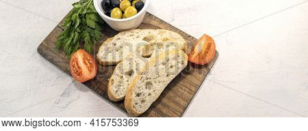 Banner With Sliced Bread On Serving Board Served With Olives, Tomatoes, And Fresh Herbs On White Tab