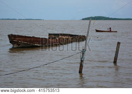Bluff, Nicaragua. 03-17-2019. A Boat Sank On The River While A Fishermen Is Rowing On A Boat In The