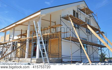 Modern House Repair And Renovation. Plastering, Applying Stucco And Painting The Facade Walls Using