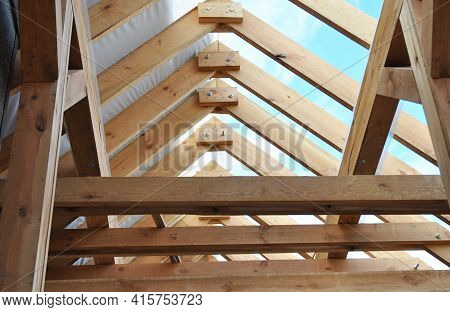 Wooden Roof Framing With A Close-up Of Rafters, Roof Beams And Purlins Framing During Roofing Constr