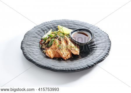 Teppanyaki Style Salmon - Grilled Salmon Fillet with Soy Sauce and Vegetables. Japanese Teppanyaki Salmon Steak garnished with lemon and green beans leaf. Black asian plate on white background